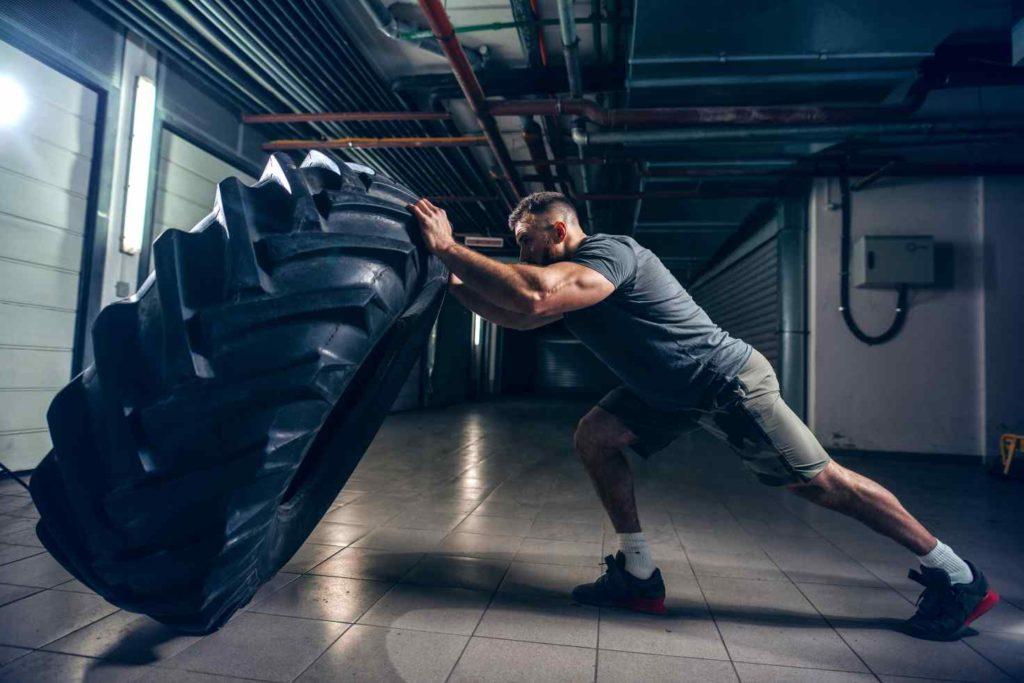 Mann hebt Treckerreifen beim Crossfit Training